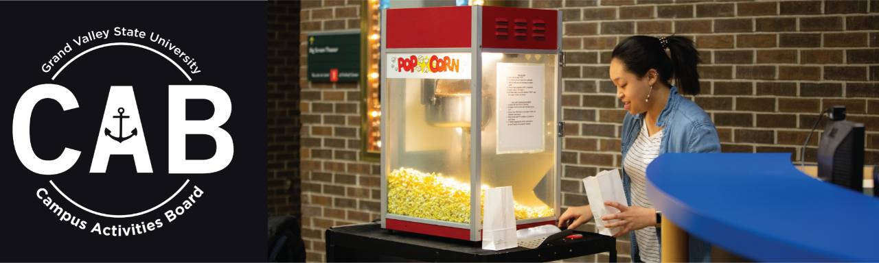 Campus Activities Board. Campus Activities Board member popping popcorn for a movie premiere.